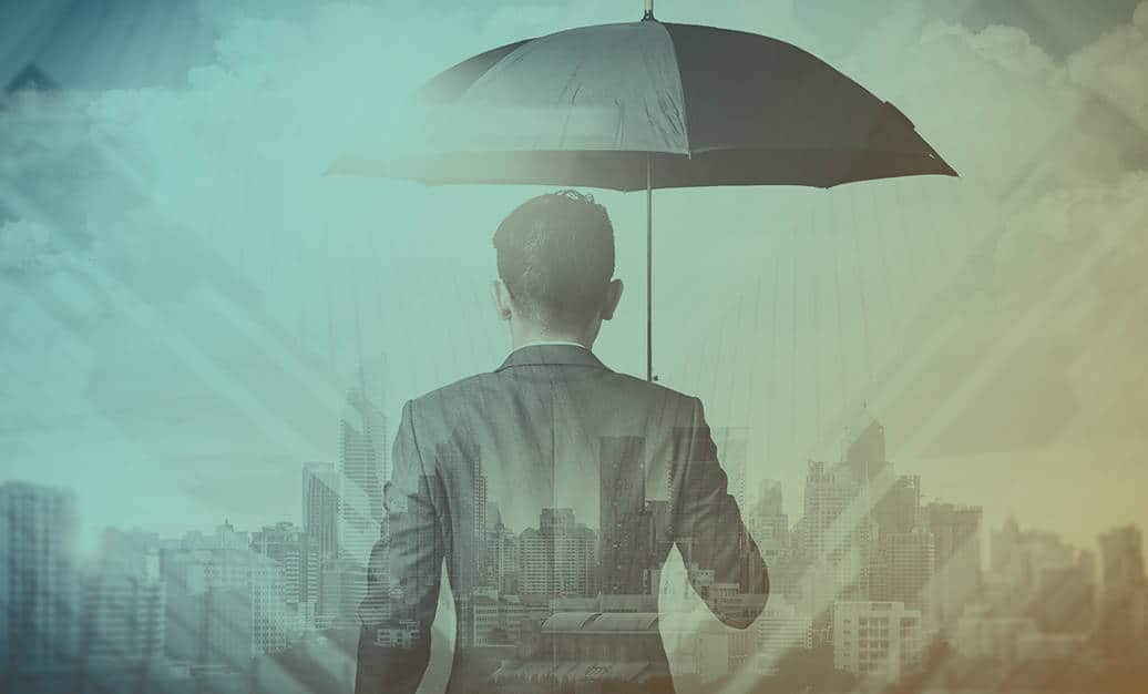 Business executive holds an umbrella and faces towards a cityscape